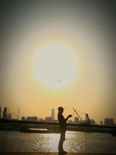 Silhouette man fishing at river against clear sky