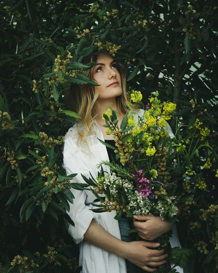 Portrait of beautiful young woman standing by flowering plants