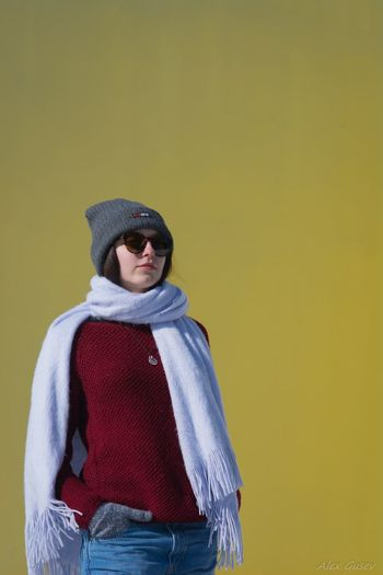 Woman Wearing Warm Clothing While Standing Against Colored Background
