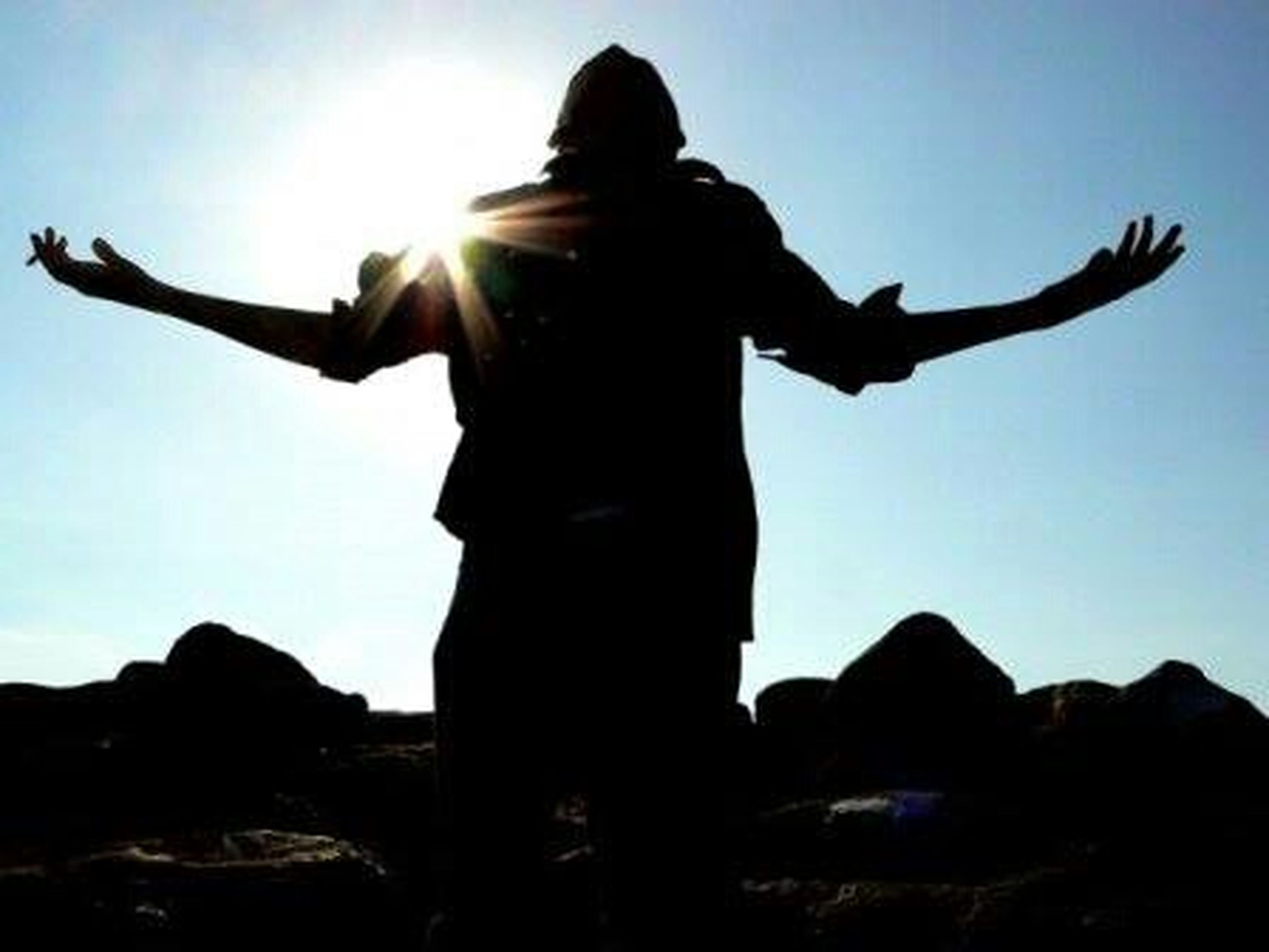 silhouette, sun, lifestyles, leisure activity, low angle view, standing, sky, sunbeam, full length, sunlight, arms outstretched, clear sky, lens flare, three quarter length, young adult, tranquility, rock - object, arms raised