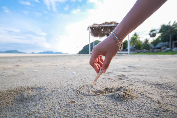 Vacations Beach Beauty In Nature Close-up Day Holding Human Body Part Human Finger Human Hand Nature One Person Outdoors People Real People Sand Sea Shell Sky Water Write On Sand