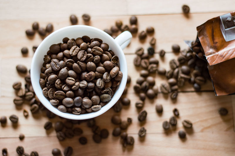 Directly above view of roasted coffee beans scattered by cup on table