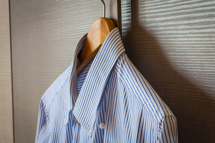 Close-up of striped shirt hanging coathanger by wooden wall