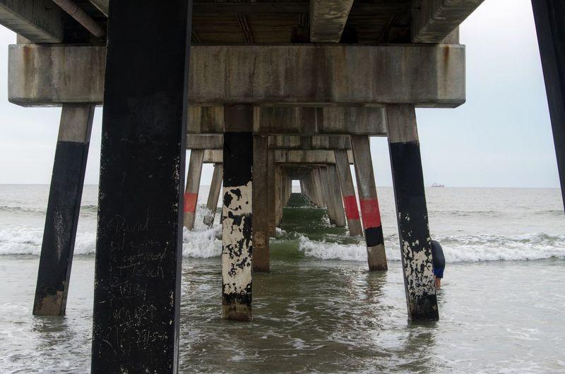 Underneathn view pier by sea