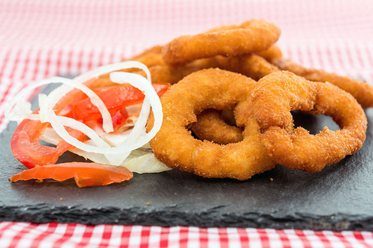 Close-up of onion rings on slate at table