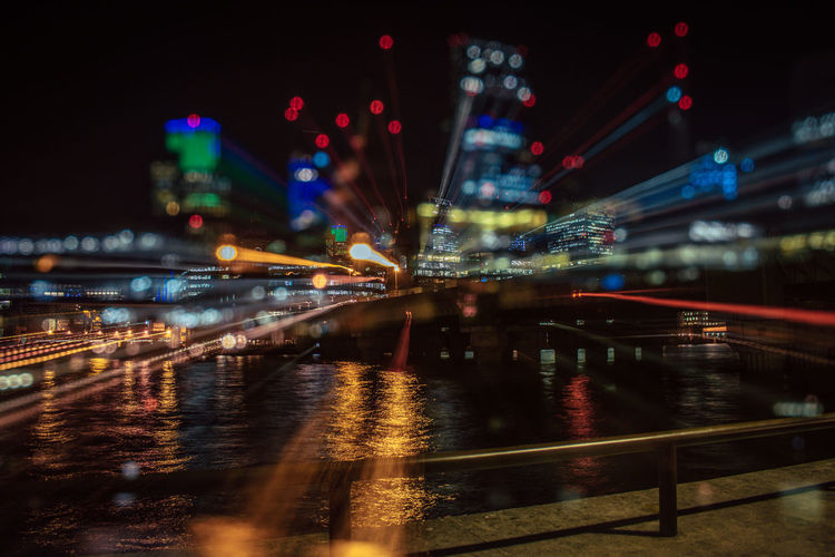 Architecture Bridge - Man Made Structure Building Exterior Built Structure City City Life Cityscape Illuminated Light Trail Long Exposure Modern Night No People Outdoors River Sky Skyscraper Transportation Travel Destinations Urban Skyline Water Connected By Travel