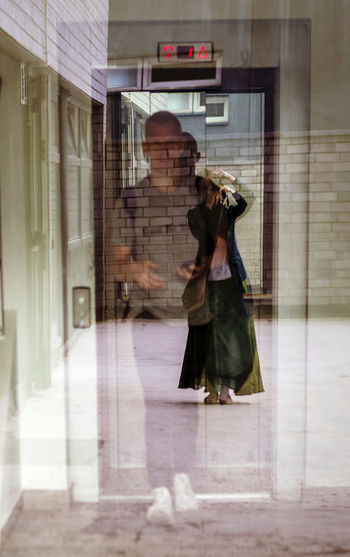 Woman photographing with reflection on glass
