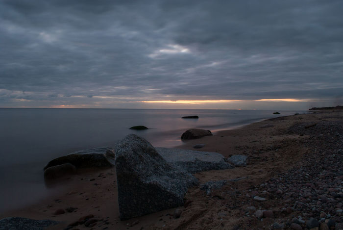 This rock, that is almost in the center caught my eye, it was different, it was luring me in. I like things that are out of an ordinary. And also you can see my girlfriend's ghost walking on the right. Beach Beauty In Nature Calm Cloud Cloud - Sky Dramatic Sky Horizon Over Water Idyllic Majestic Nature Non-urban Scene Remote Rock - Object Scenics Sea Seascape Shore Sky Sunset Tourism Tranquil Scene Tranquility Travel Destinations Vacations Water