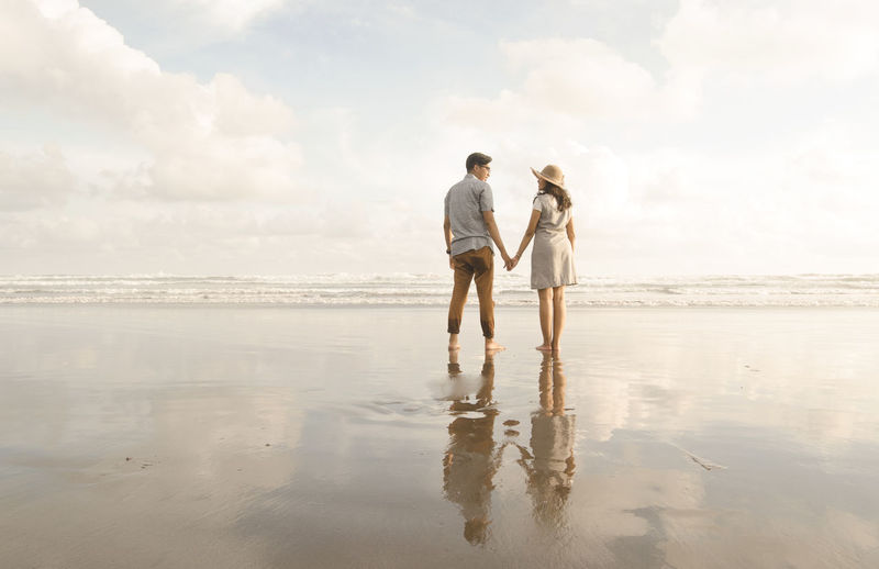 Rear View Of Couple Holding Hands At Beach Against Sky