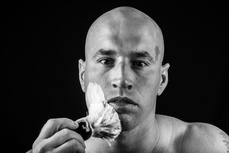 Close-up portrait of shirtless bald man applying shaving cream against black background