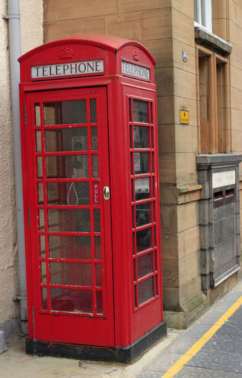 Red telephone booth on street in city