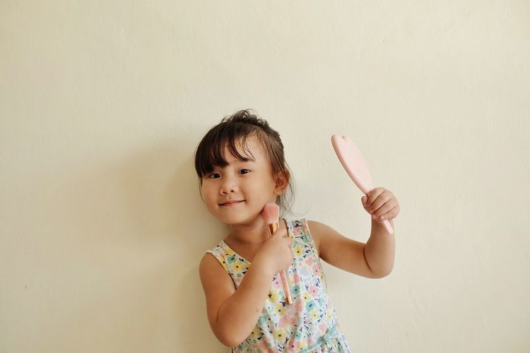 Little girl is make up and hold a brush, cheeks and mirrors. Child Kids Girl Make Up Mirror Brush Cheek Beauty Child Childhood One Person Offspring Wall - Building Feature Girls Portrait Looking Innocence Indoors  Smiling Females Front View Cute Copy Space Waist Up Headshot