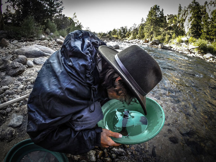 Man looking at water in bowl by stream
