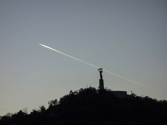 Liberty Statue, Budapest Contrail Gellért Hill Silhouette Clear Sky Contrail Day Dusk Evening Gellért Hegy Iconic Liberty Statue Liberty Statue Budapest Low Angle View Nature No People Outdoors Silhouette Sky Sunset Travel Destinations Tree Vapor Trail