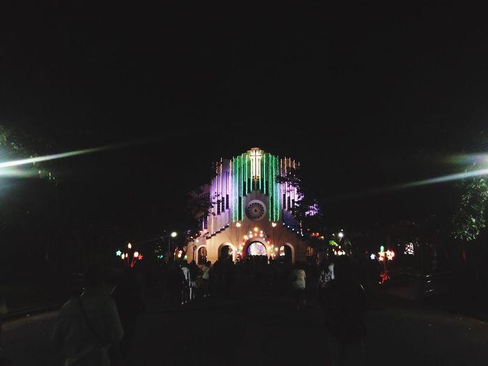 Crowd at illuminated city against sky at night