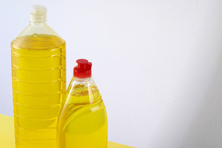 Close-up of yellow glass bottle on table against wall