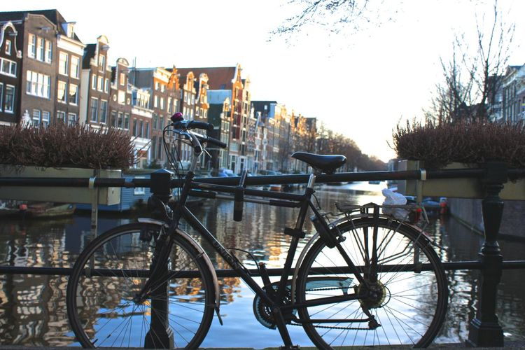 Bikes in Amsterdam Architecture Bicycle Bridge - Man Made Structure Building Exterior Built Structure Canal City Clear Sky Mode Of Transport No People Outdoors Parked Railing River Transportation Travel Travel Destinations Water Your Amsterdam