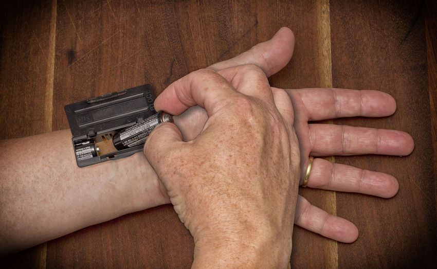 Cropped image of man putting battery on hand over wooden table