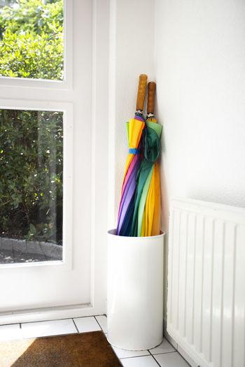 Close-up of multi colored umbrellas on glass window