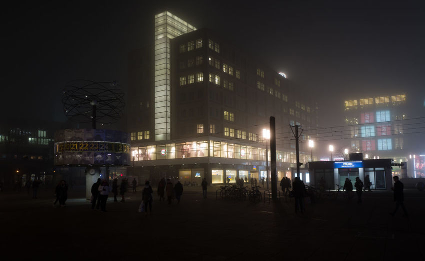 People in illuminated city against sky at night