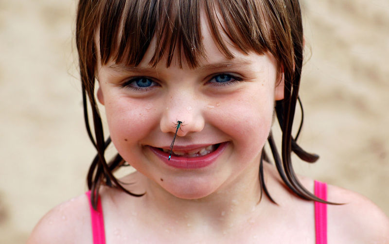 Blue Eyes Bangs Brown Hair Child Childhood Close-up Cute Emotion Females Focus On Foreground Front View Girls Hairstyle Happiness Headshot Innocence Insect Looking At Camera Offspring One Person Outdoors Portrait Smiling