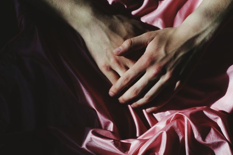 Cropped image of hands on pink textile