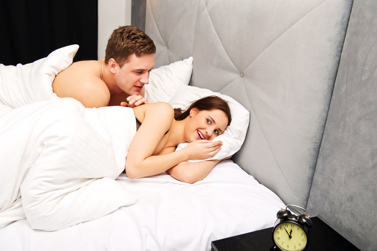 Affectionate couple in bed at home