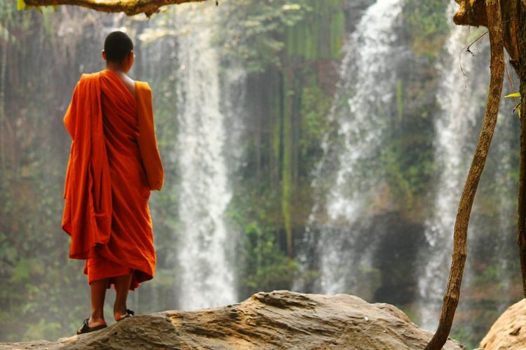 Rear view of buddhist monk standing in front of waterfall
