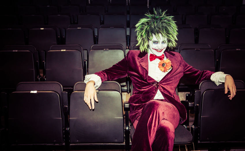 A male cosplayer dressed as The Joker from the Batman and DC Comics movie franchise at a common con event in Sheffield, UK Batman Comicon Cosplay DC DC Comics Evil The Joker Adult Character Comic Con Cosplayer Cosplayers Crazy Fancy Dress Indoors  Joker Male Movie Theater One Person Outfit Portrait Real People Seat Sitting Villain