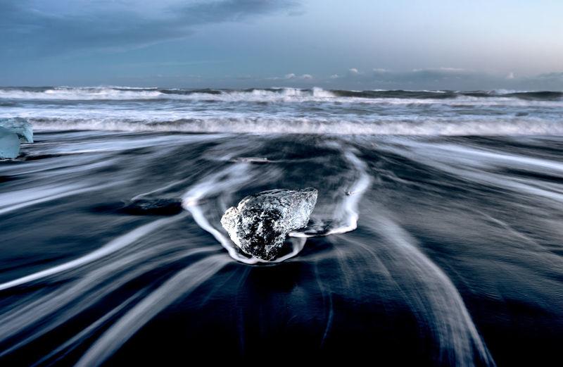 Long exposure of waves in sea against sky