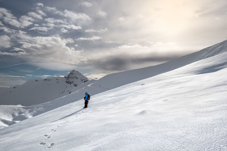 Side view of man skiing on snowcapped mountains against sky