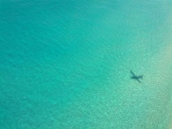 Schattenspiel  with Airplane over clear Sea at Fraser Island