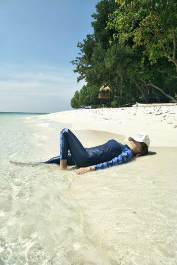 On the Sea Beach Beauty In Nature Day Full Length Land Leisure Activity Lifestyles Lying Down Lying On Back Nature One Person Outdoors Real People Relaxation Resting Sea Sky Water Young Adult