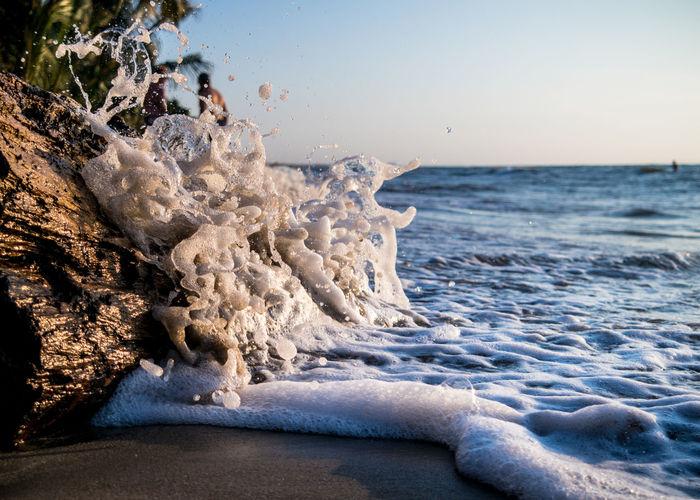 Sea waves splashing on beach against clear sky