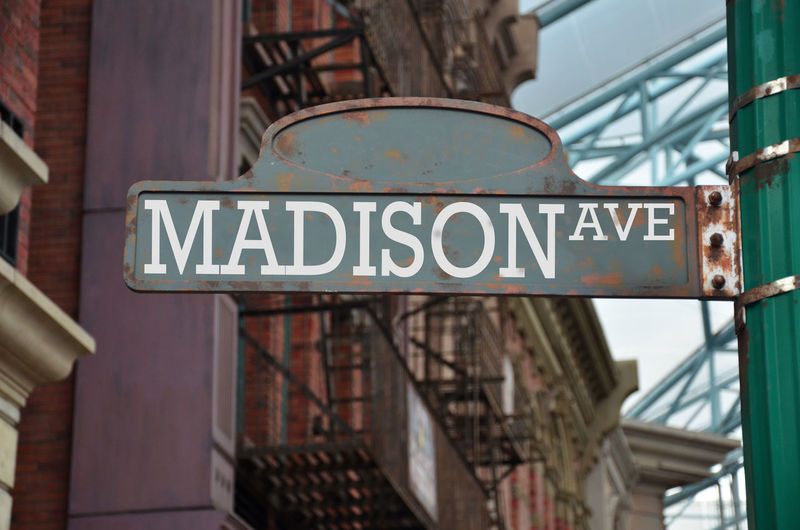 Low angle view of madison avenue sign against buildings in city