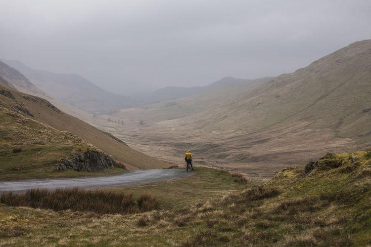Man riding bike on mountain against sky
