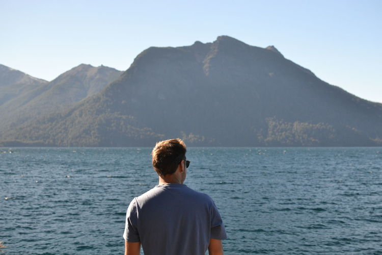 Rear view of man looking at lake and mountains against clear sky