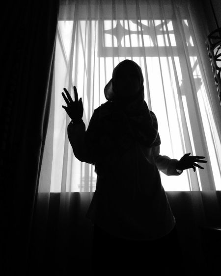 Low angle view of silhouette woman standing by window at home
