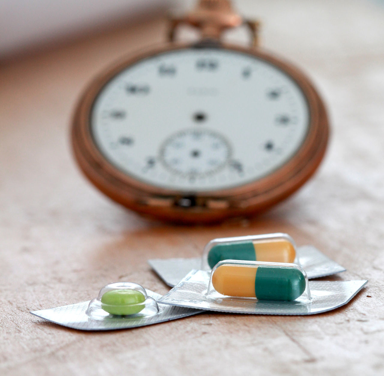 clock, time, indoors, table, close-up, no people, number, selective focus, still life, alarm clock, healthcare and medicine, focus on foreground, instrument of time, wood - material, day, accuracy, instrument of measurement, shape, pill, circle, minute hand