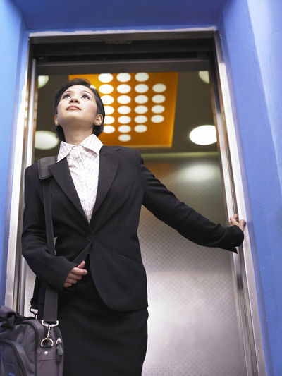 Low angle view of businesswoman exiting elevator