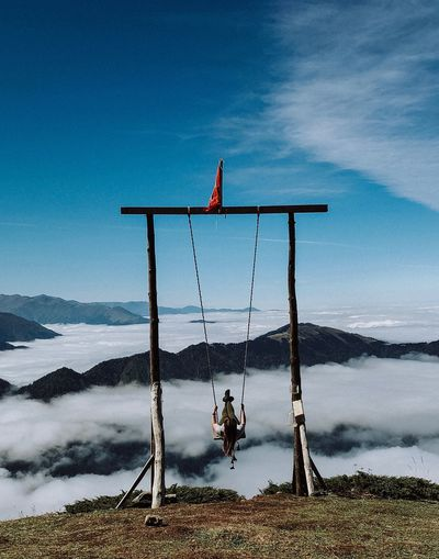 Woman Enjoying Swing At Mountain Peak Against Sky