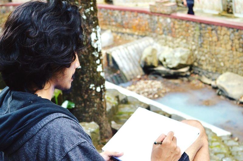 Man Drawing On Book Against Stream