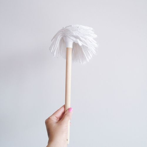 Close-up of hand holding mop over white background