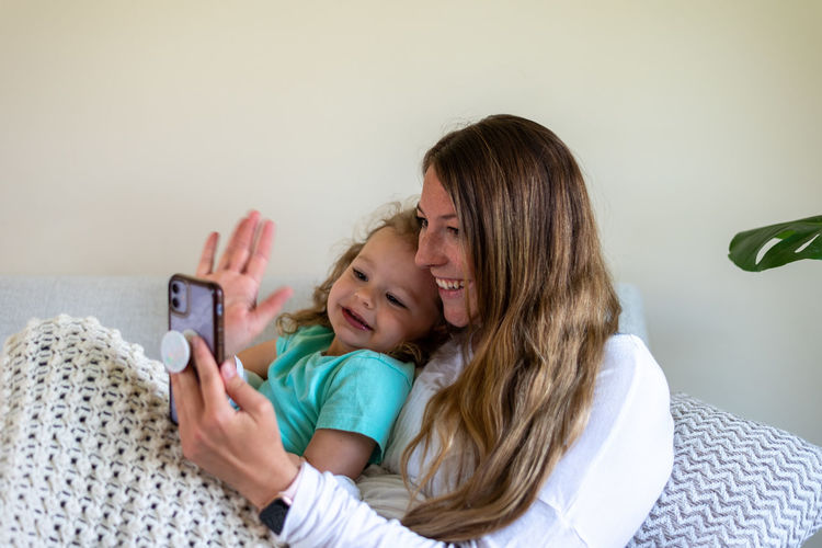 Mother and daughter while using smart phone
