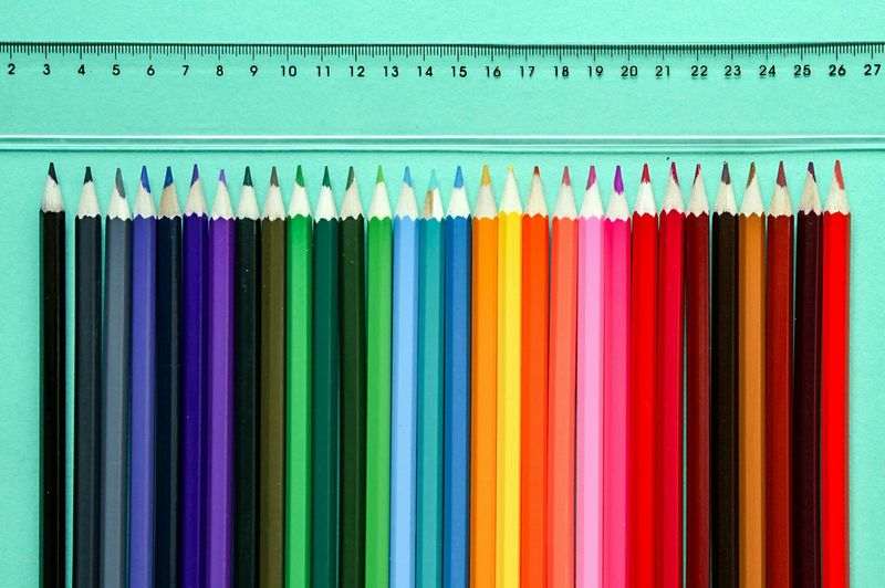 Close-Up Of Colored Pencils On Table By Ruler