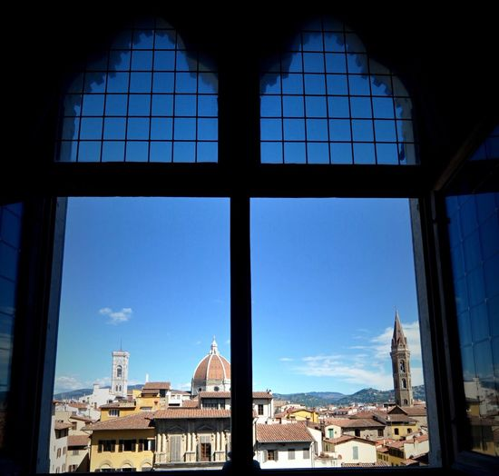 Cityscape against sky seen through window