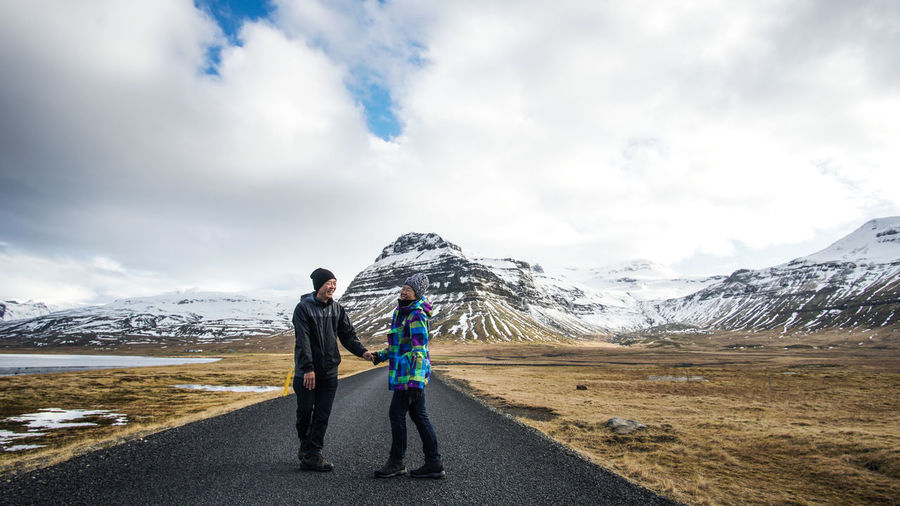 Full length of couple standing on road against cloudy sky