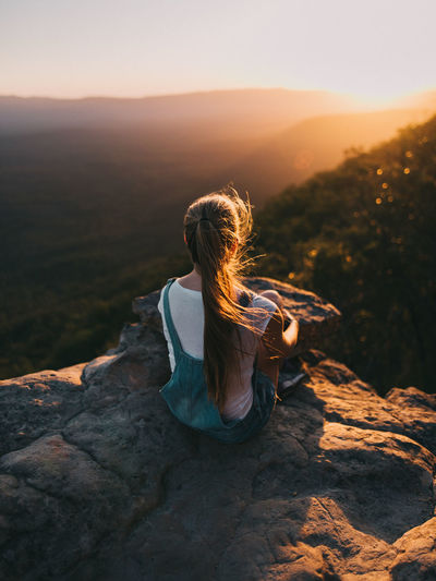 Beauty In Nature Casual Clothing Hair Hairstyle Leisure Activity Lifestyles Looking At View Nature Non-urban Scene One Person Outdoors Real People Rear View Rock Rock - Object Scenics - Nature Sky Solid Sunset Tranquility Women A New Beginning International Women's Day 2019