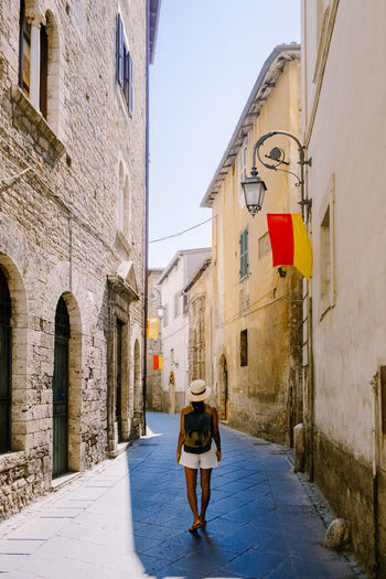 Rear view of woman walking on narrow alley amidst buildings
