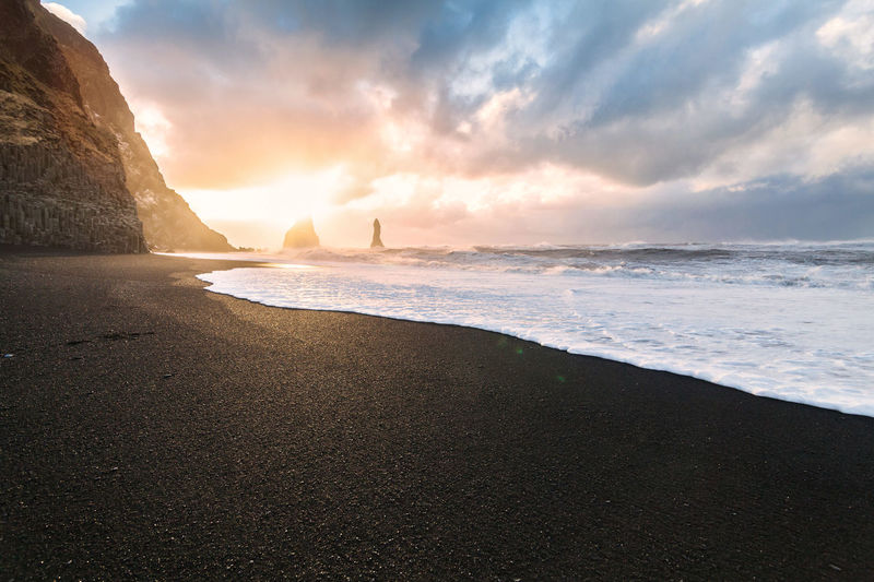 Reynisfjara or better known as Black Sand beach view during sunrise Beach Beauty In Nature Black Sand Black Sand Beach Black Sand Beach Iceland Black Sand Moments Black Sands Day Horizon Over Water Iceland Iceland Trip Icelandic Icelandic Nature Icelandtrip Nature Outdoors Reynisfjara Rock - Object Sand Scenics Sea Sky Tranquility Water ıceland